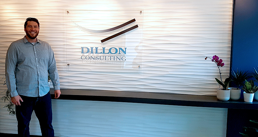 Brent Boss in front of the new Edmonton office Dillon Consulting interior sign