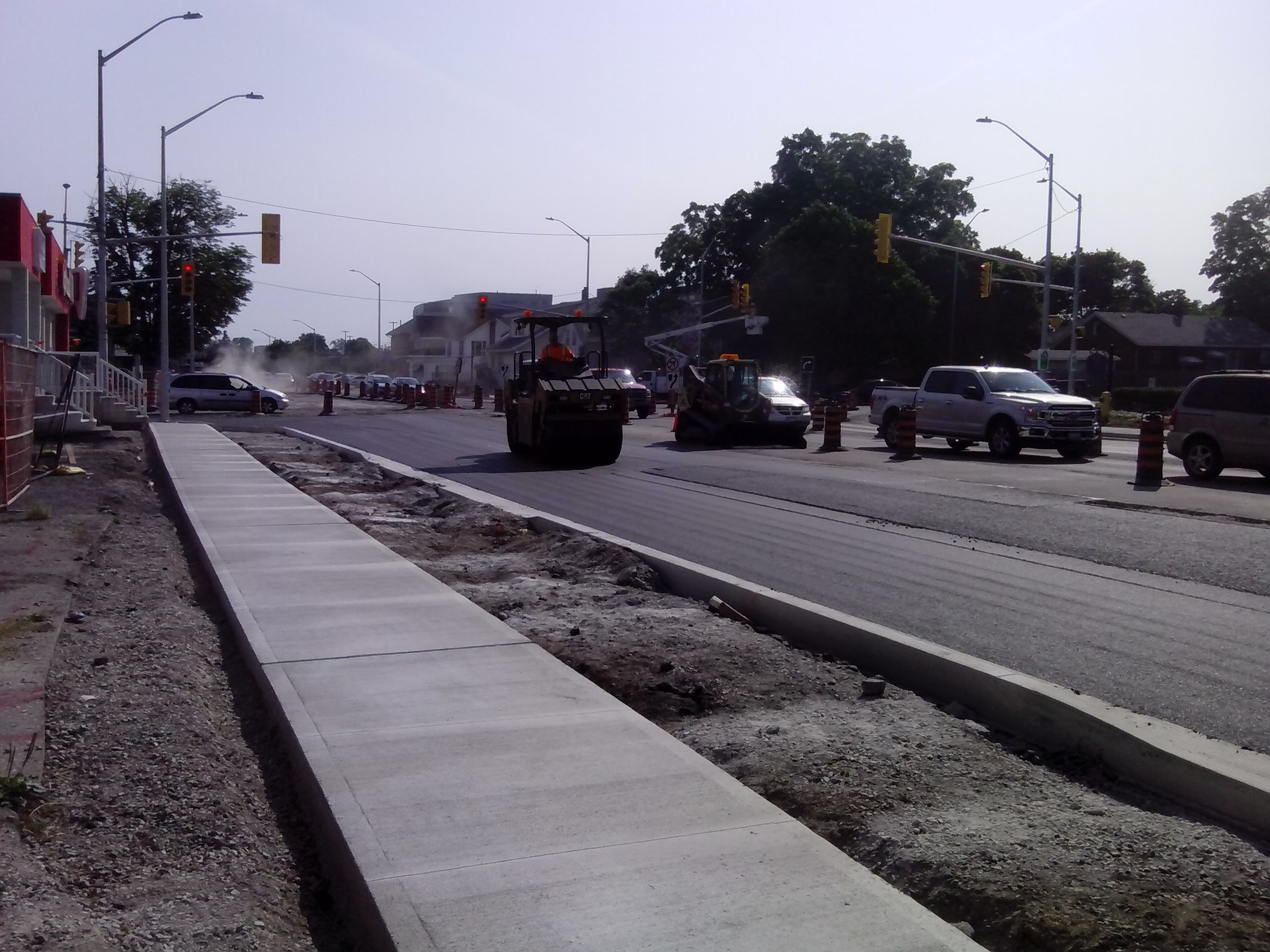 New sidewalk installed and roller flattening new pavement beside traffic