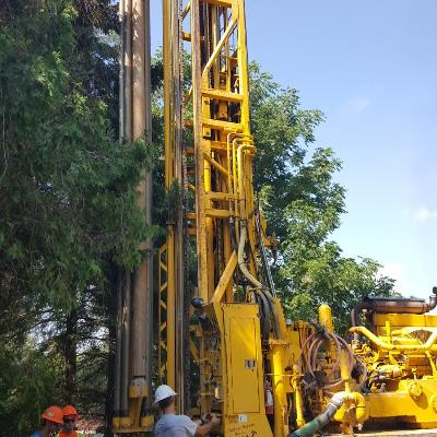 Yellow drill surrounded by men working