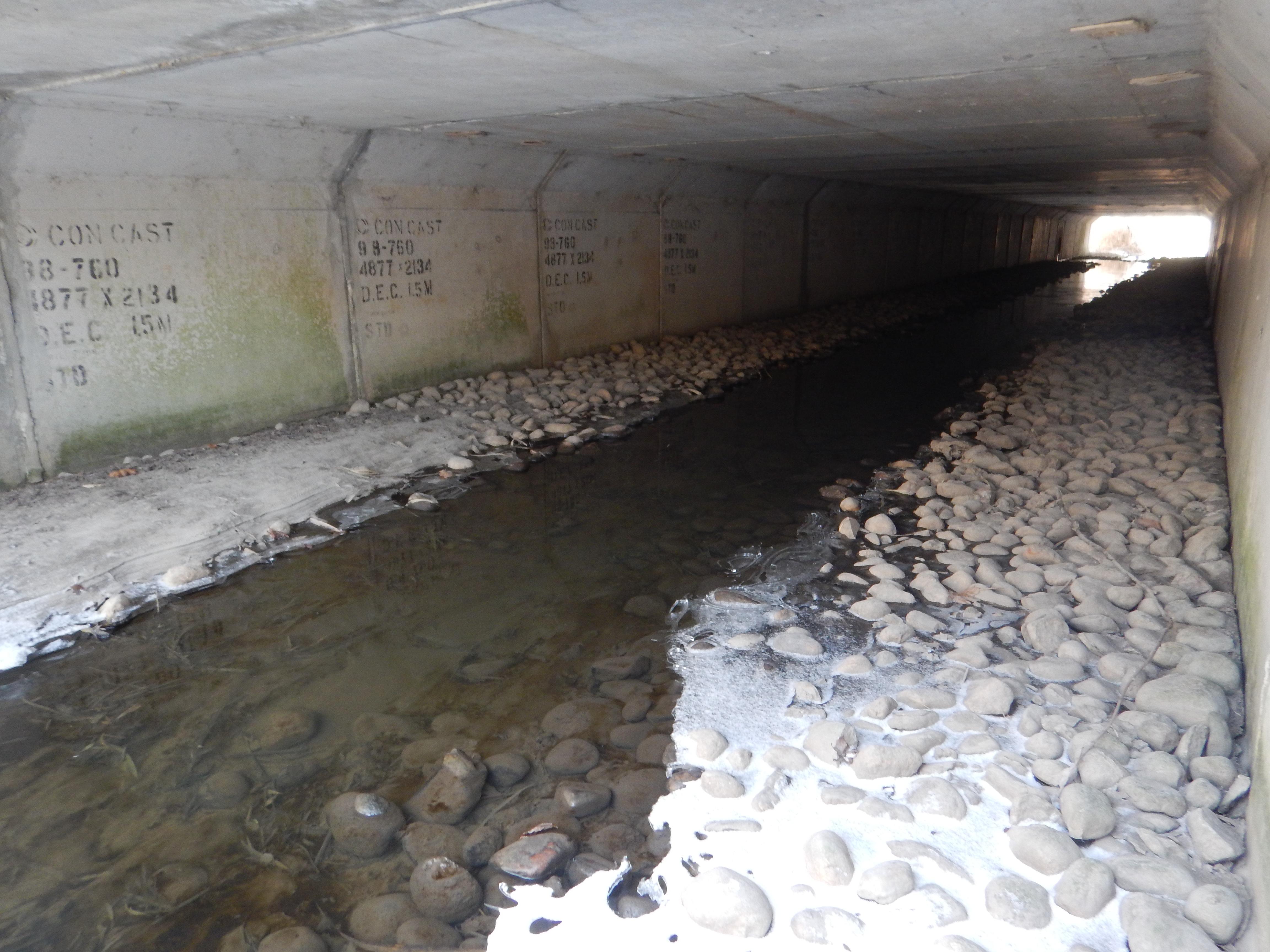 water running under cement culvert with snow around edges